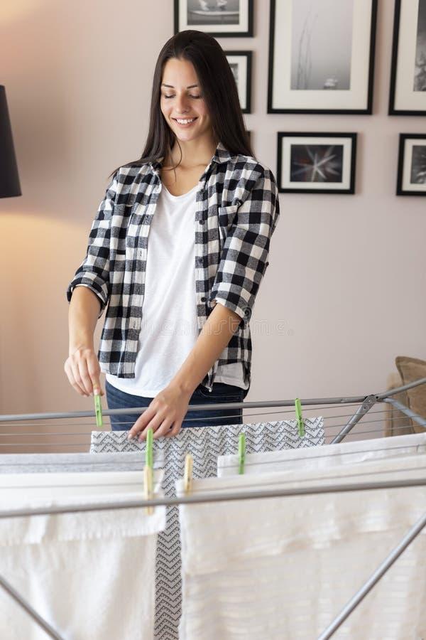Frau, welche heraus die Reinigung hängt, um zu trocknen lizenzfreie stockbilder
