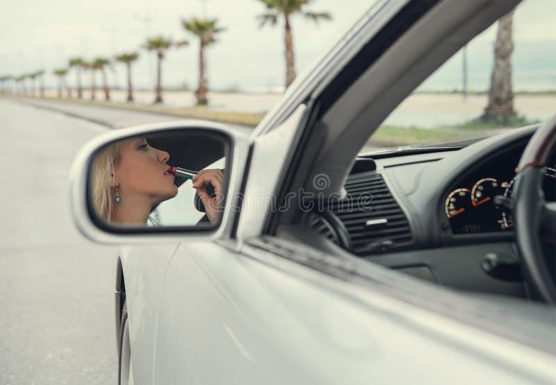 Frau wenden den Lippenstift an, der im Autospiegel der hinteren Ansicht schaut stockfoto