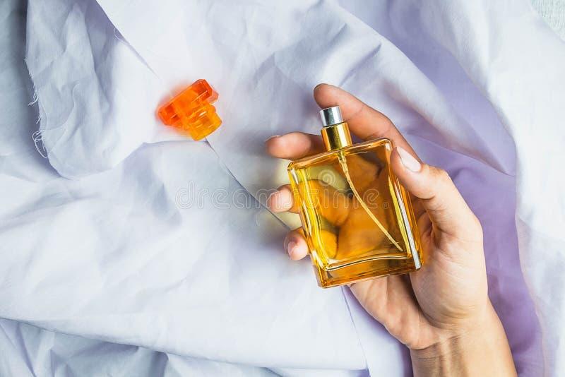Frau wendet Parfüm auf ihrem Handgelenk an stockbild