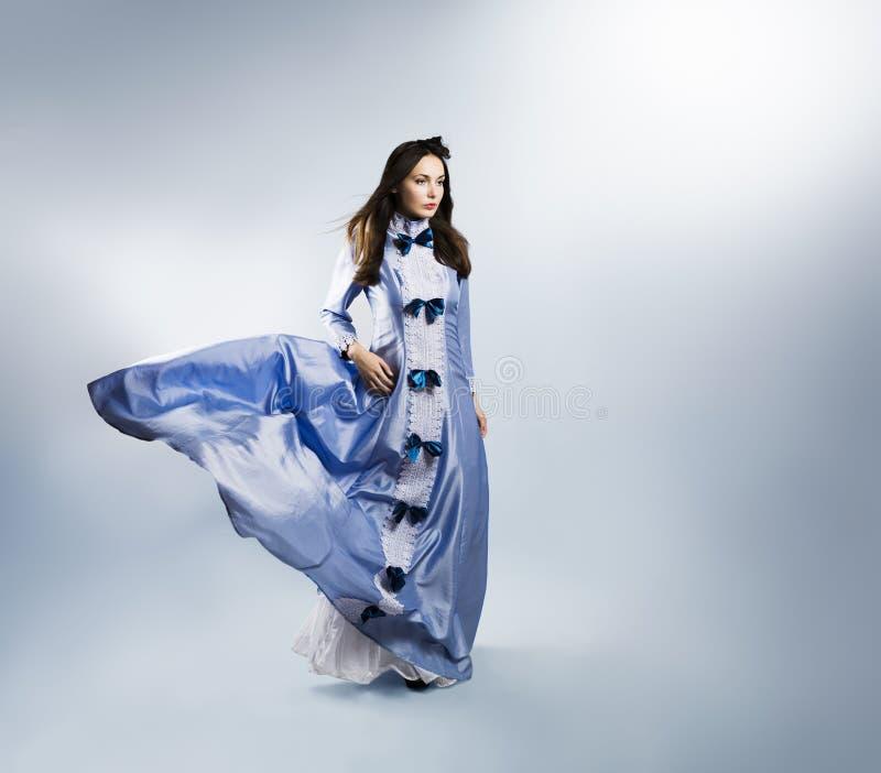 Frau, wenn purpurrotes Kleid auf Gray Backgound wellenartig bewegt wird stockfoto