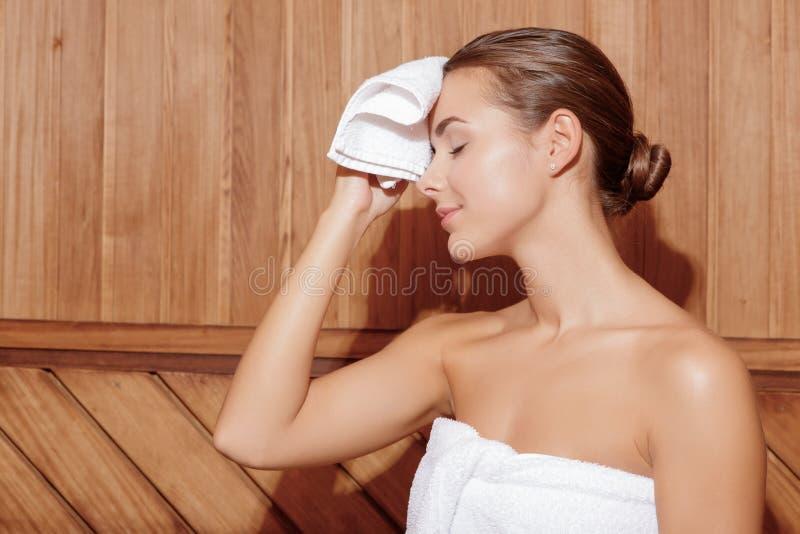 Frau wickelt ihre Stirn ein stockbild