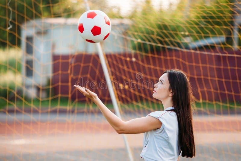 Frau wirft Fußball am Stadion auf Hintergrund des Gitters der Fußballziele stockbild