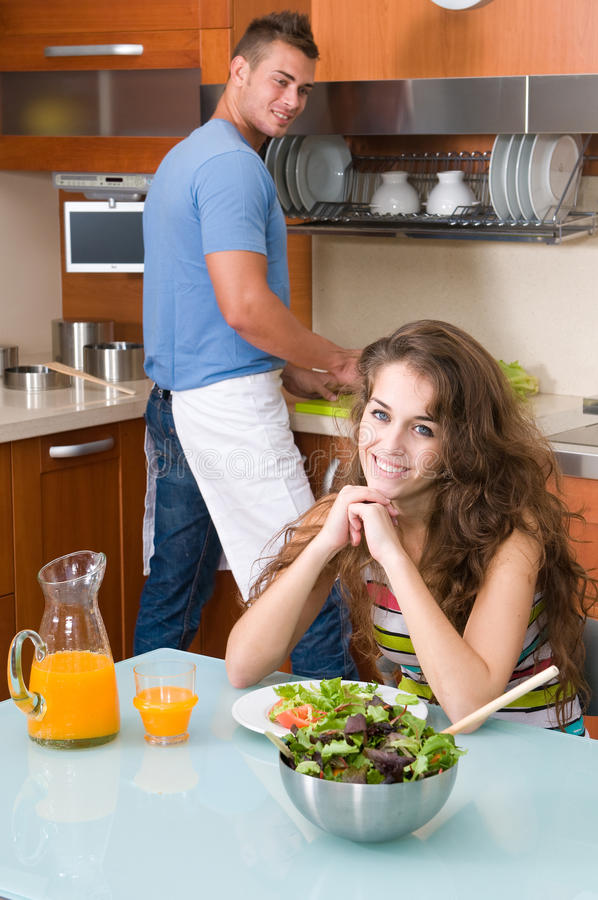 Frau wirh Salat in der Küche- und Manreinigung stockbild