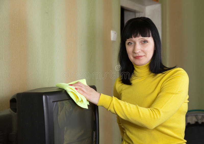 Frau wischt den Staub auf Fernsehapparat ab stockbild