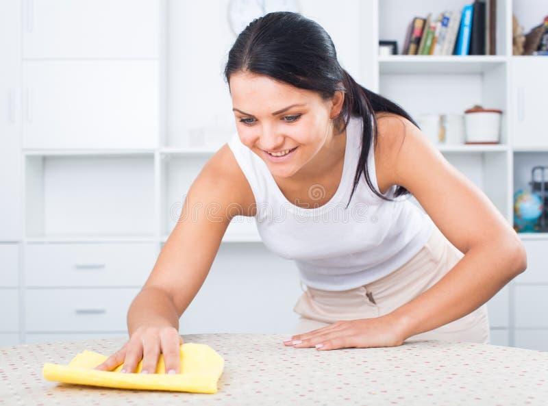 Frau wischt Möbel vom Staub ab lizenzfreies stockbild