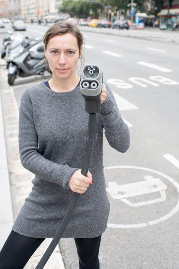 Frau zahlt an einer Ladestation des Elektroautos stockfotografie