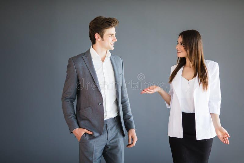 Frau zeigt etwas, das zu ihrem Teilhaber abstrakt ist Kopieren Sie Raum zwischen zwei Geschäftspersonen, die nach strengem Kleidk lizenzfreie stockfotografie
