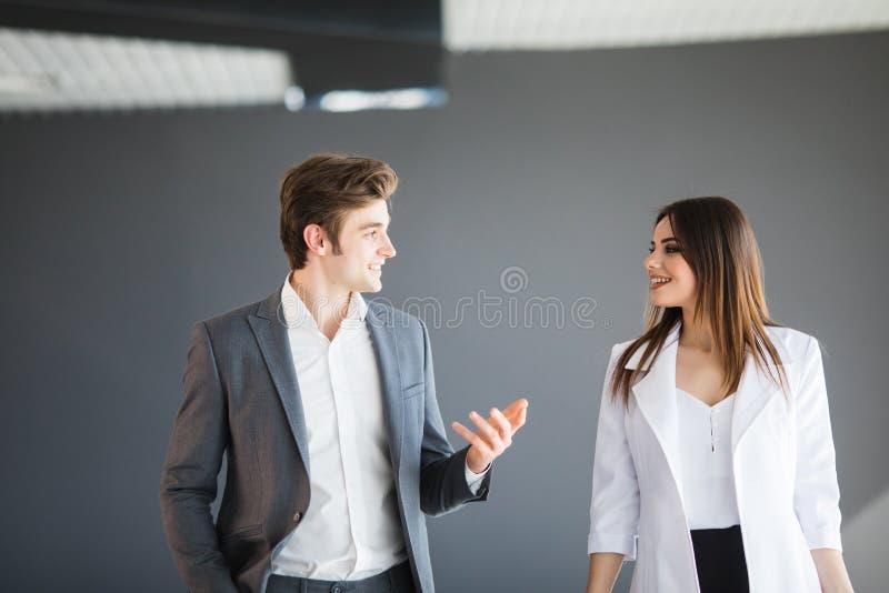 Frau zeigt etwas, das zu ihrem Teilhaber abstrakt ist Kopieren Sie Raum zwischen zwei Geschäftspersonen, die nach strengem Kleidk stockfotografie