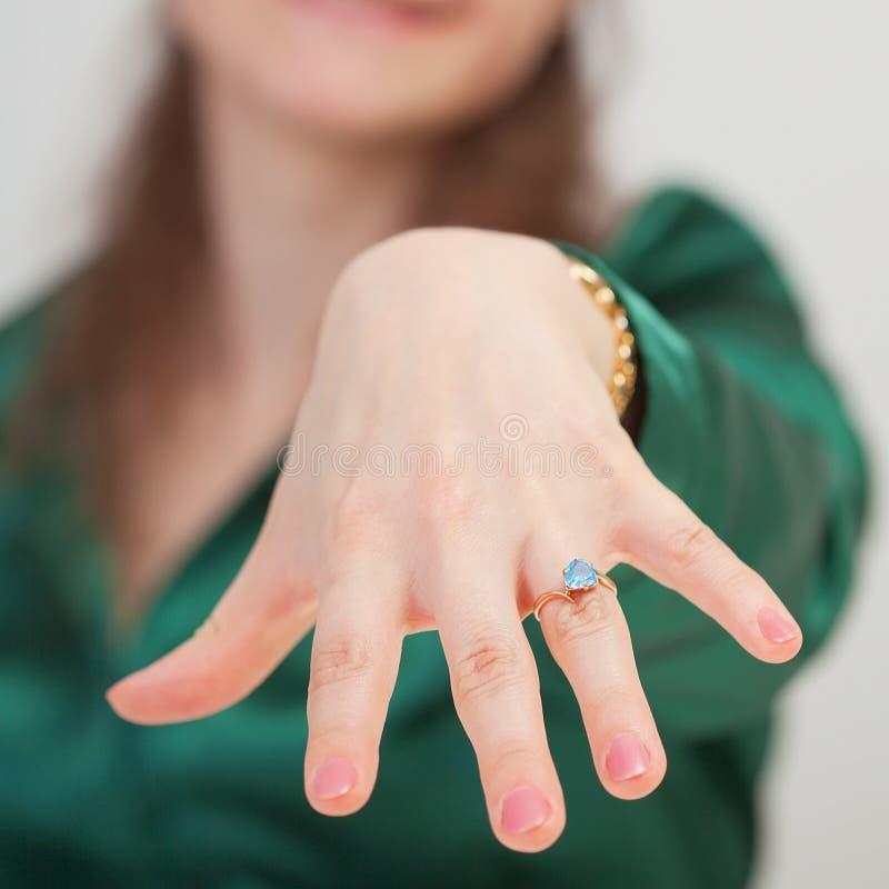 Frau zeigt neuen Ring mit blauem Edelstein stockfotografie