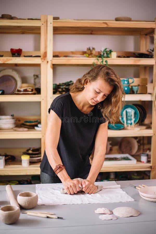Frau zerknittert Stück weißen Lehm für sculpting lizenzfreie stockbilder