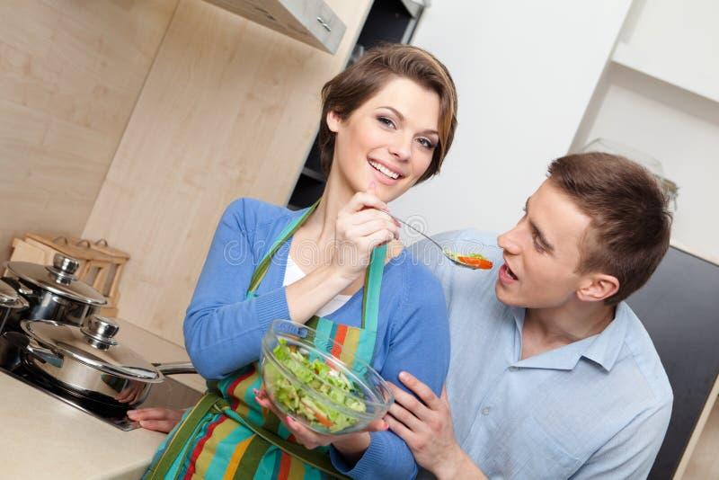 Frau zieht ihren Ehemann mit Salat ein lizenzfreie stockbilder