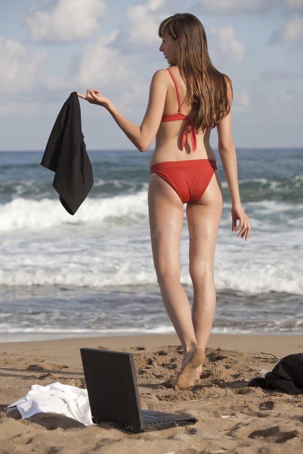 Frau zieht sich auf dem Strand aus stockbild