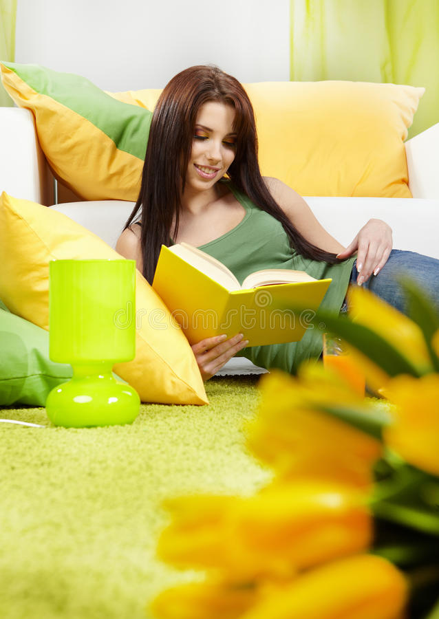 Frau zu Hause, die ein Buch liest stockbild