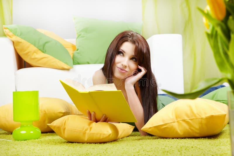 Frau zu Hause, die ein Buch liest lizenzfreie stockbilder