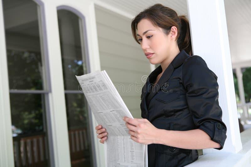 Frau zu Hause, die Zeitung liest stockfotos