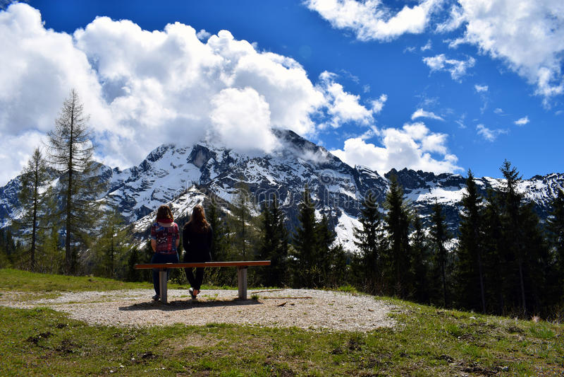 Frau zwei, die auf Bank und aufpassendem schönem Bergblick von deutschen Alpen sitzt lizenzfreie stockfotos