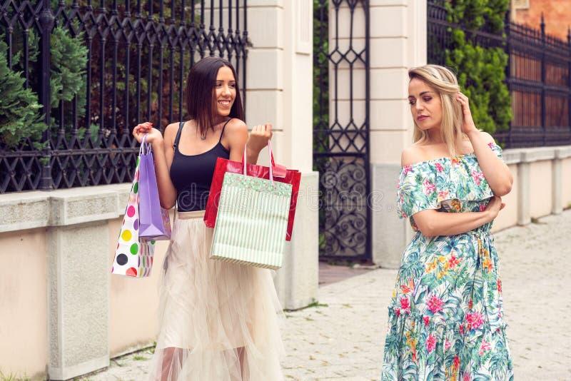 Frau zwei, die am Einkaufen in der Stadt argumentiert lizenzfreies stockbild