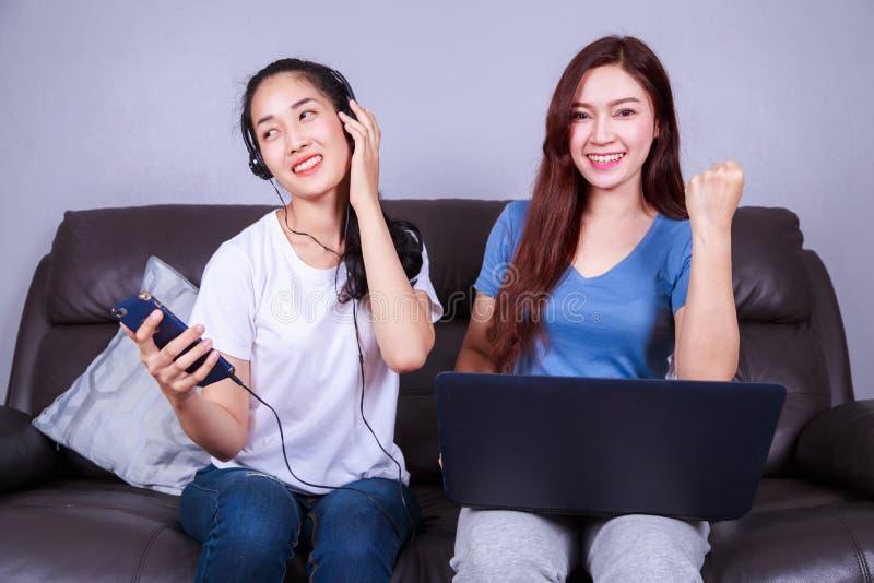 Frau zwei, die Laptop-Computer verwendet und Musik im headph hört lizenzfreie stockfotos