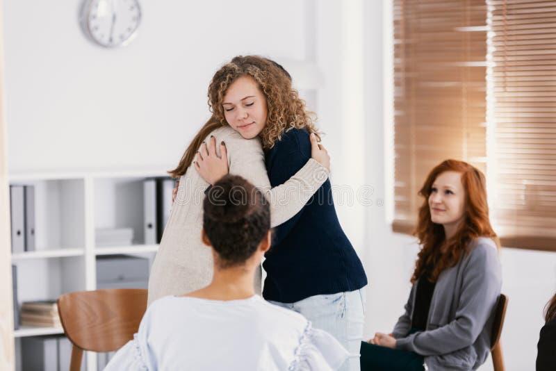 Frau zwei, die w?hrend der Psychotherapie f?r Missbrauchsopfer sich tr?stet stockfotografie