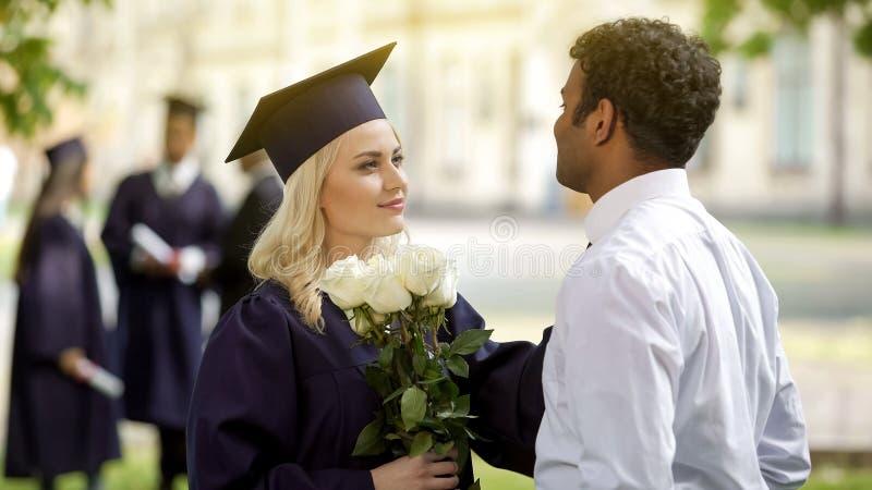 Frauabsolvent in den akademischen Insignien mit Blumen sprechend mit Freund, Bildung lizenzfreie stockfotografie