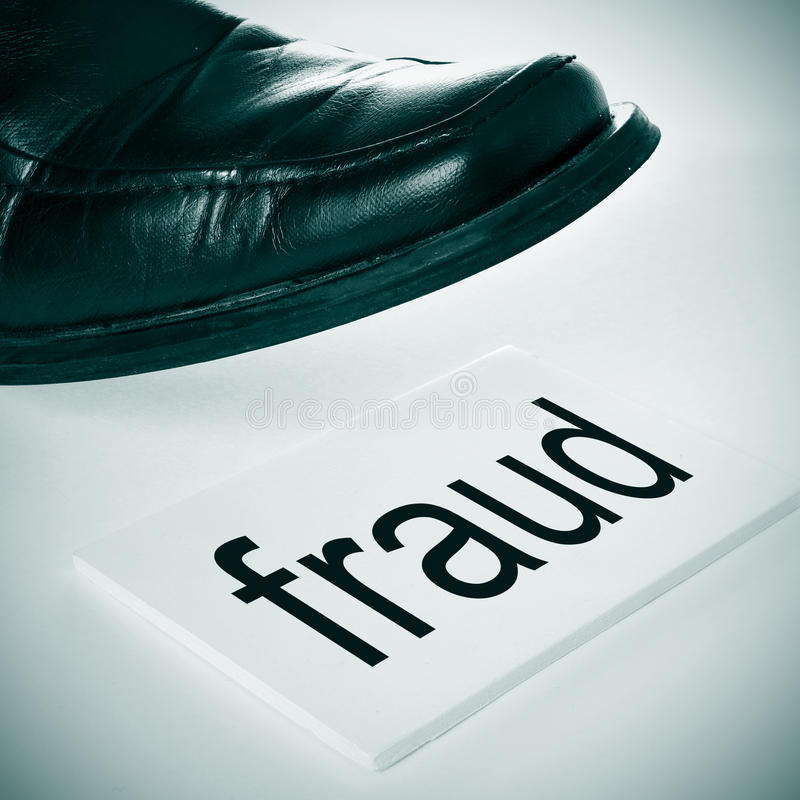 Fraud. A man foot wearing a black shoe stepping in a signboard with the word fraud written in it royalty free stock photo