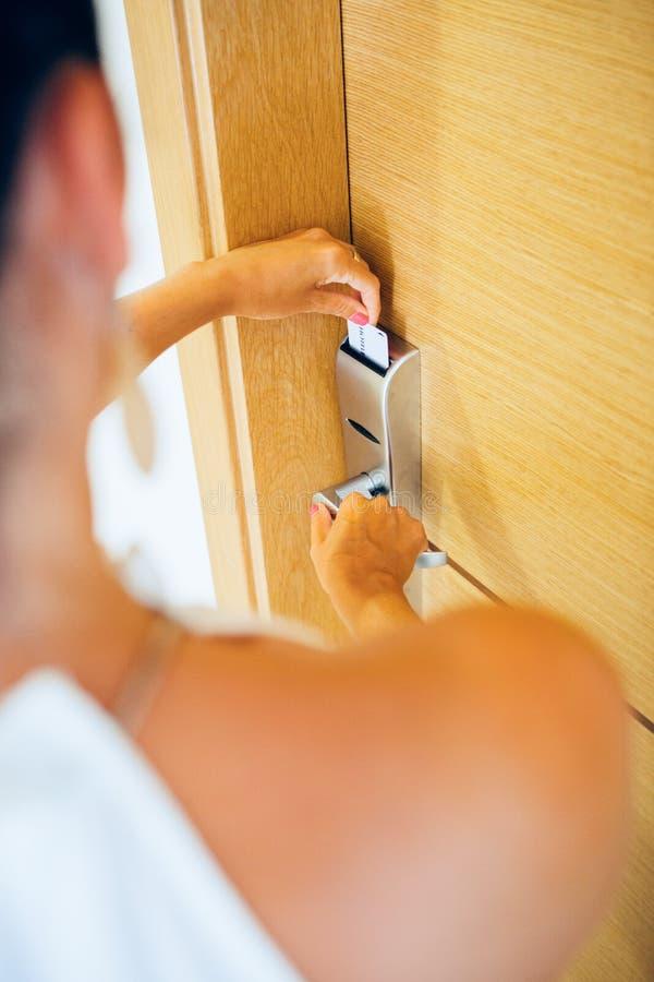 Frauenöffnungstür mit Schlüsselkarte lizenzfreie stockbilder