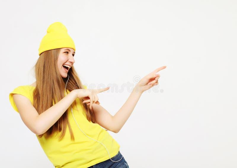Frauenüberraschung, die Produkt zeigt Schönes Mädchen mit dem langen Haar zeigend auf die Seite Darstellen Ihres Produktes lizenzfreies stockbild