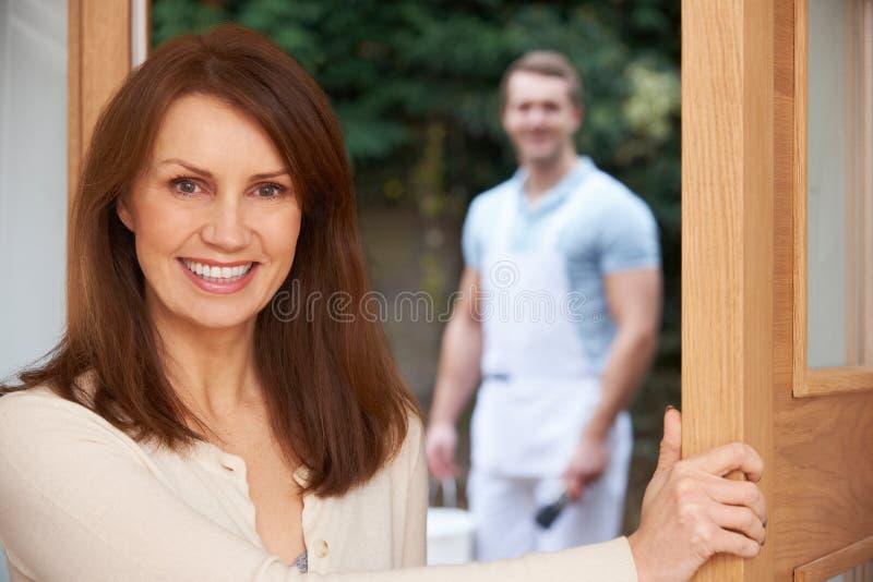 Frauen-Öffnungs-Tür zum Dekorateur lizenzfreie stockbilder
