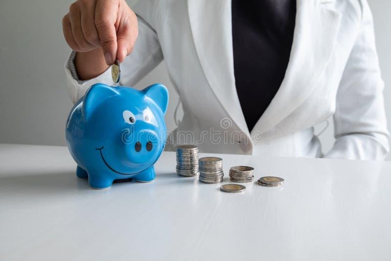 Frauen übergeben das Setzen der Münze in Rettungsgeld des blauen Sparschweins mit Münzenstapel stockfotografie