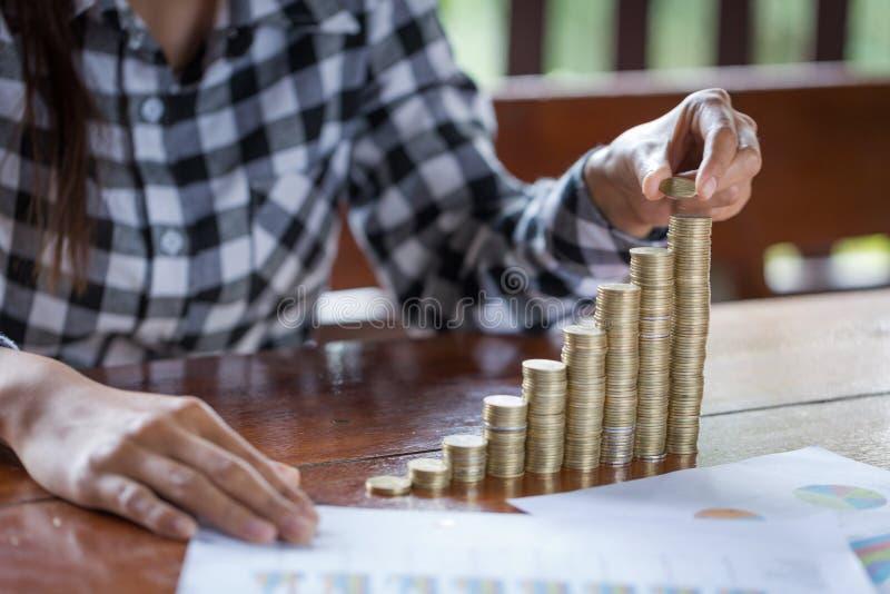 Frauen übergeben gesetzte Geldmünzen zum Stapel Münzen Geschäfts-Wachstum Co lizenzfreie stockfotos