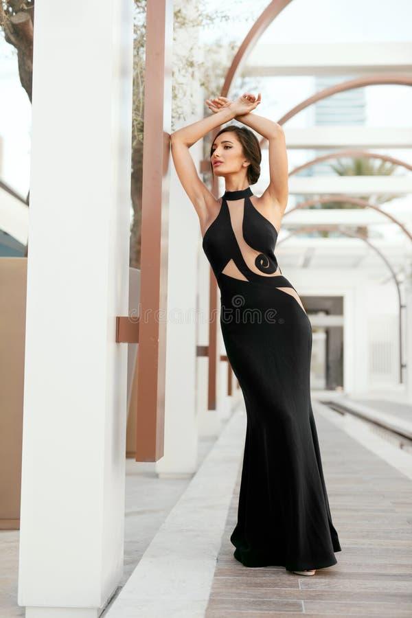 Frauen-Art Mode-Mädchen im langen schwarzen Kleid, das draußen aufwirft lizenzfreie stockbilder