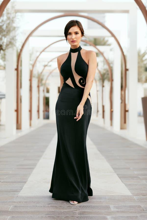 Frauen-Art Mode-Mädchen im langen schwarzen Kleid, das draußen aufwirft stockbild