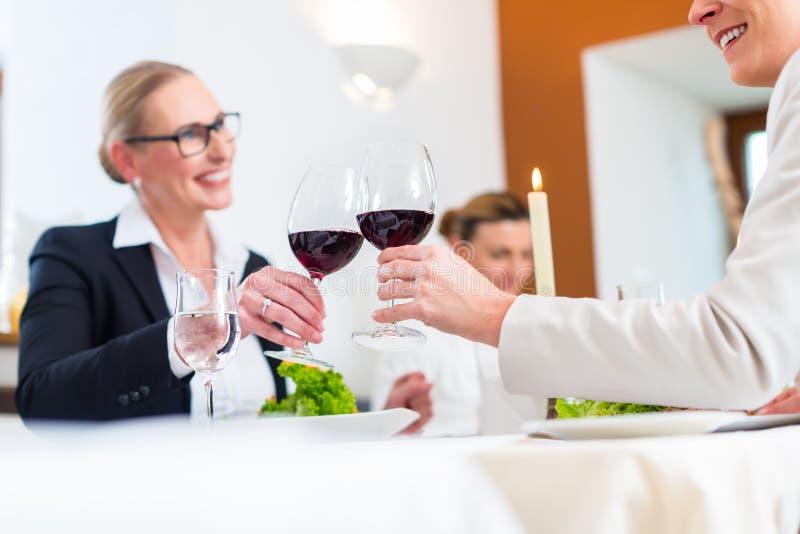 Frauen auf Business-Lunch röstend mit Wein lizenzfreies stockbild