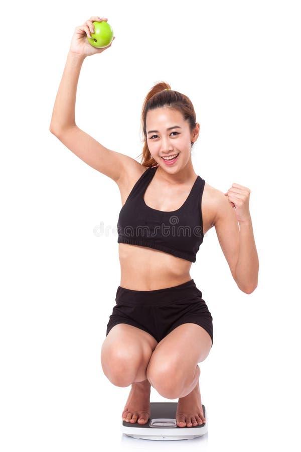 Frauen auf Skala zujubelnd für das Erzielen ihres Gewichtsverlustziels lizenzfreies stockfoto