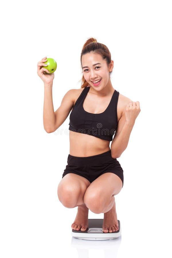 Frauen auf Skala zujubelnd für das Erzielen ihres Gewichtsverlustziels stockbild