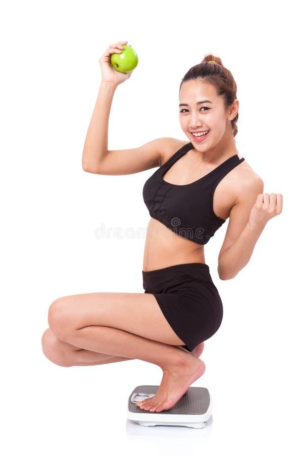 Frauen auf Skala zujubelnd für das Erzielen ihres Gewichtsverlustziels stockfotografie