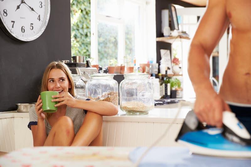 Frauen-aufpassendes Mann-bügelndes Hemd in der Küche stockfoto