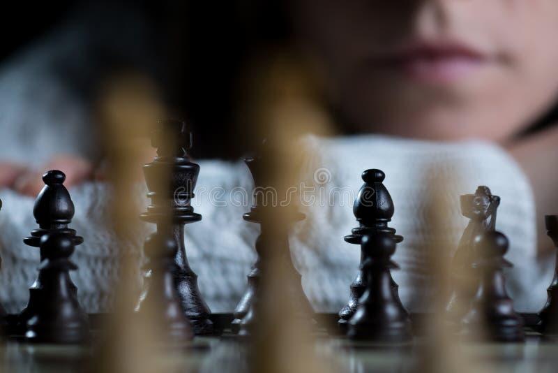 Frauen-aufpassendes Schachbrett stockfotografie