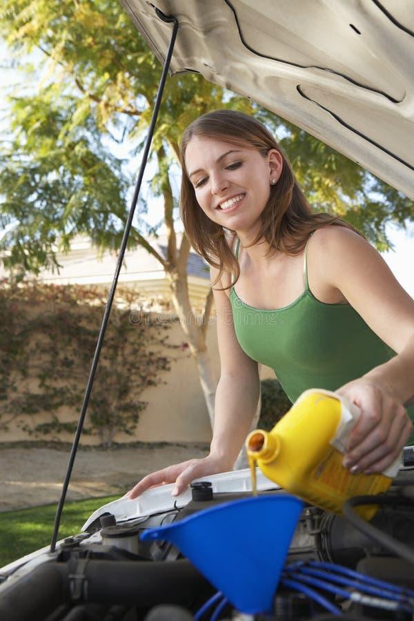 Frauen-auslaufendes Öl in Automotor lizenzfreie stockfotografie
