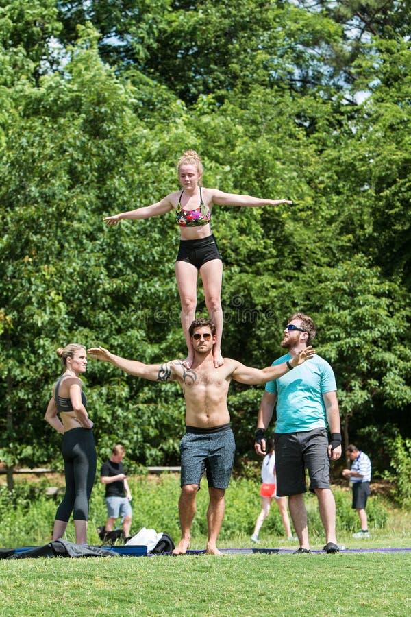 Frauen-Balancen auf Schultern des Mann-übenden Programms im Park stockfoto