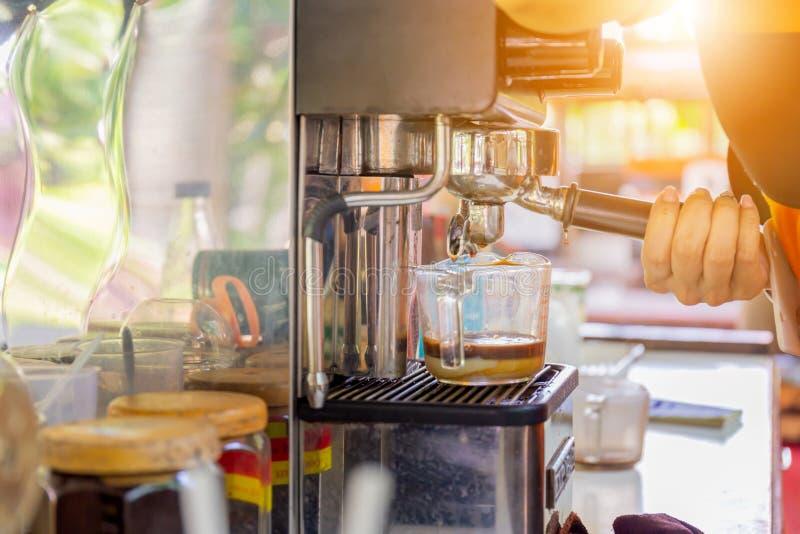 Frauen barista Hand unter Verwendung des automatischen vorbereitenden frischen Kaffees der Kaffeemaschine und Gießen in Glasschal stockfotografie