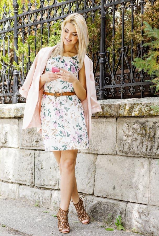 Frauen benutzen das Telefon draußen in der Stadtstraße Porträt des jungen lächelnden Modemädchens, das mit Telefon steht lizenzfreie stockfotografie