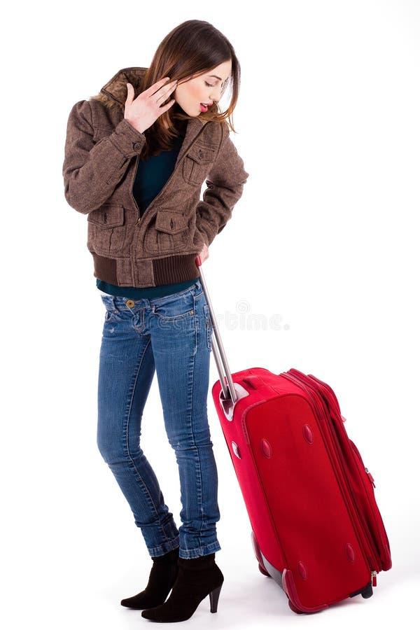 Frauen betriebsbereit zur Reise und zum Schauen ihres Gepäcks stockbild