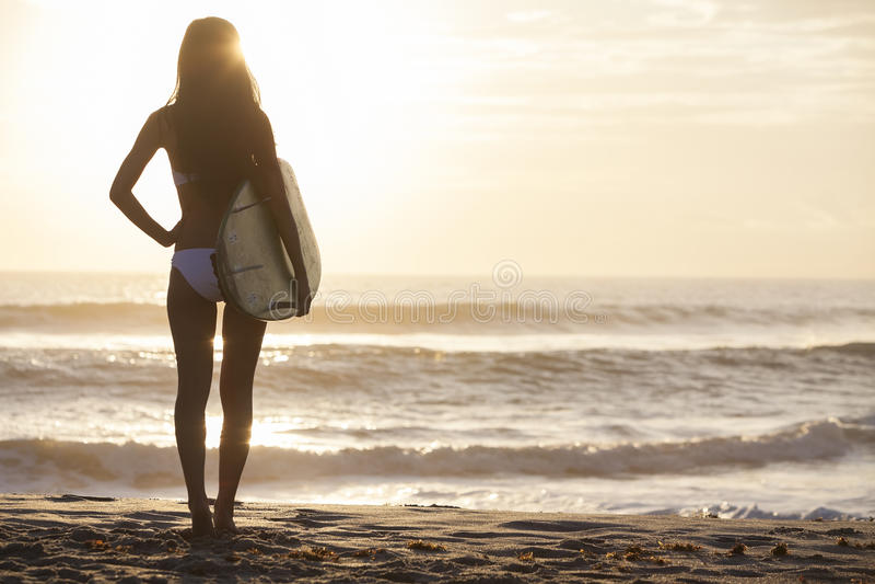 Frauen-Bikini-Surfer u. Surfbrett-Sonnenuntergang-Strand lizenzfreie stockbilder
