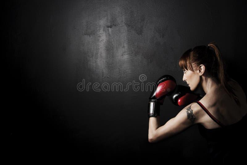 Frauen-Boxer mit roten Handschuhen auf schwarzem Backgound lizenzfreie stockfotografie