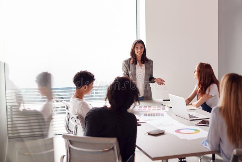 Frauen-Chef präsentiert sich in einem modernen Büro in einem Team von jungen Geschäftsfrauen, das sich am Tisch trifft stockbild