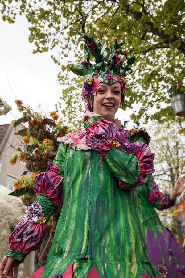 Frauen in den bunten Kleidern gehend auf Stelzen an der traditionellen Blumenparade Bloemencorso von Noordwijk nach Haarlem im Ne lizenzfreie stockfotos