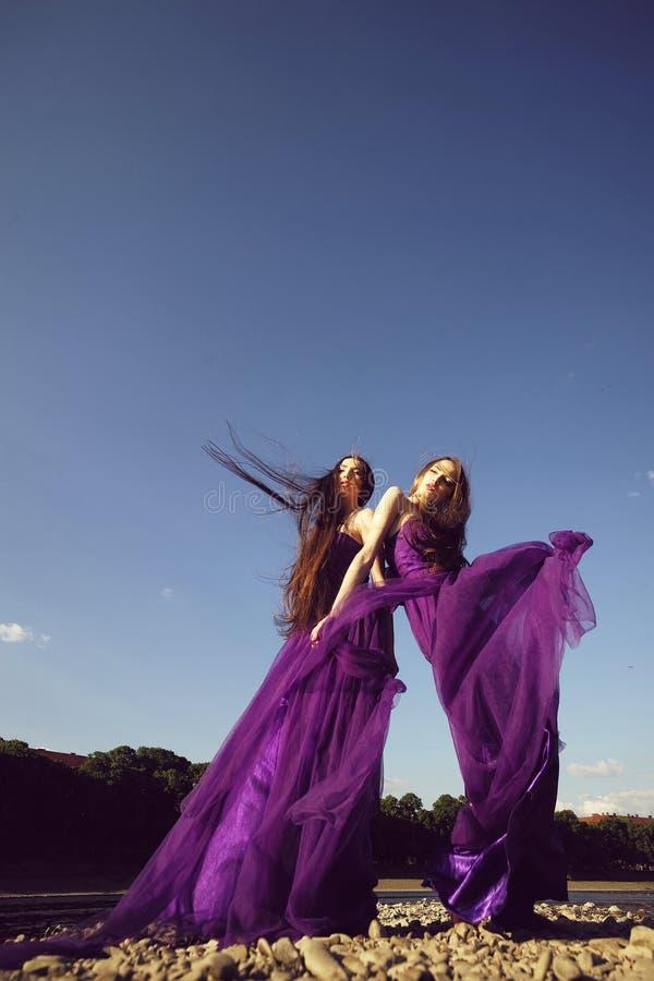 Frauen in den violetten Kleidern lizenzfreie stockfotografie