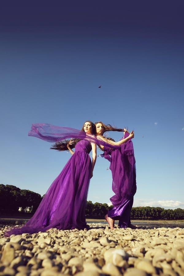 Frauen in den violetten Kleidern lizenzfreie stockfotos