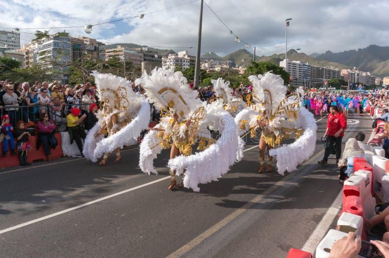 Frauen in den weißen Kostümen von den Federn, die vor der Menge tanzen lizenzfreie stockfotos
